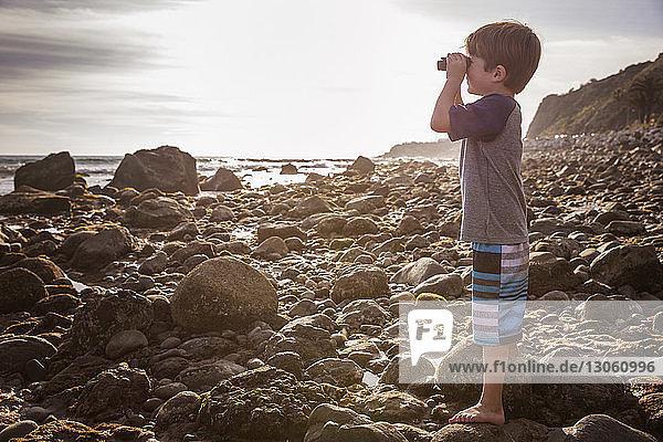 Seitenansicht eines Jungen  der durch ein Fernglas auf den Strand schaut