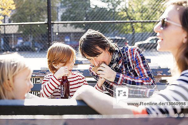 Vater isst Sandwich  das vom Sohn gehalten wird  während er mit der Familie im Park sitzt