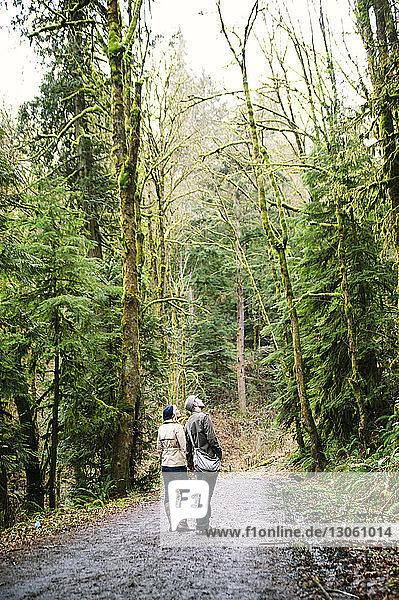 Ehepaar schaut auf  während es im Wald auf der Straße steht