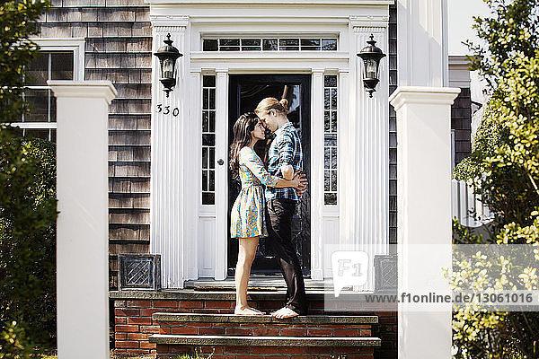 Paar umarmt sich  während es auf einer Treppe vor der Bücke steht
