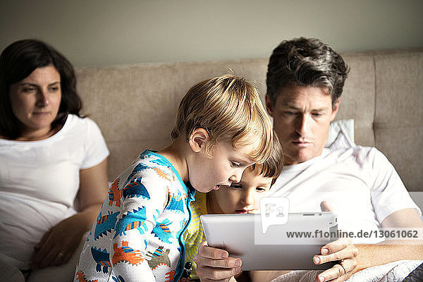 Woman looking at man using tablet computer with children on bed at home
