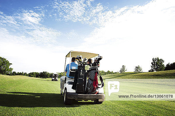 Rear view of friends riding in golf cart in field against sky