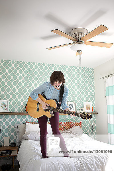 Happy woman playing guitar while standing on bed at home