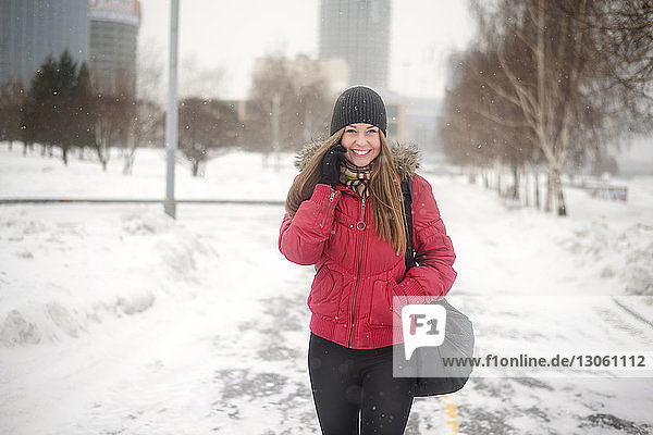 Happy young woman talking on mobile phone while walking on road during winter
