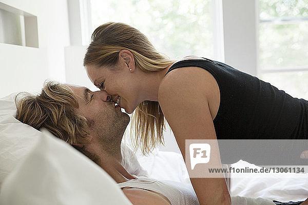 Seitenansicht eines Paares  das sich küsst  während es zu Hause auf dem Bett liegt