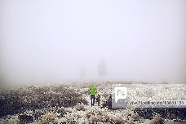 Wanderer und Hund stehen bei nebligem Wetter auf schneebedecktem Feld