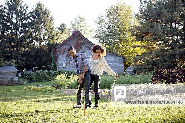 Krocketspiel eines Paares auf Grasfeld