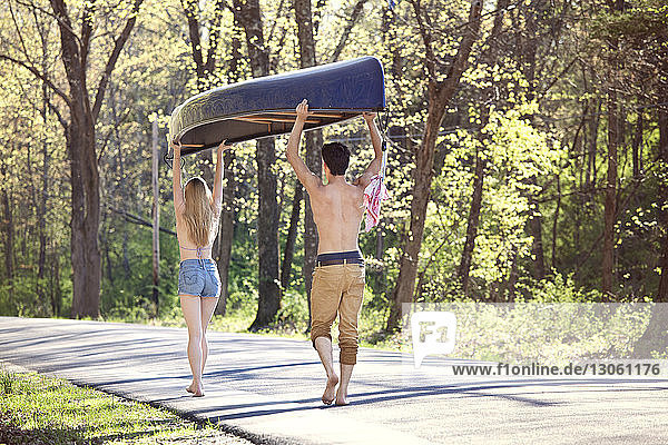 Rear view of couple carrying rowboat while walking on road in forest