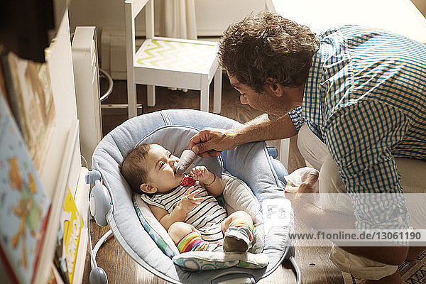 Father feeding popsicle to baby girl at home