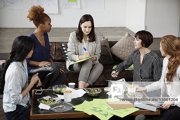 Businesswoman discussing strategy with female colleagues in creative office