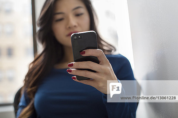 Woman text messaging while sitting at office