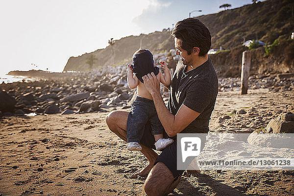 Glücklicher Vater legt seinem Sohn am Strand das Hemd hin