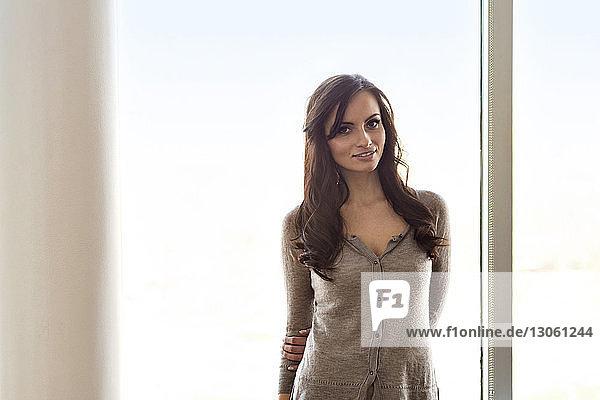 Porträt einer lächelnden Frau am Fenster stehend