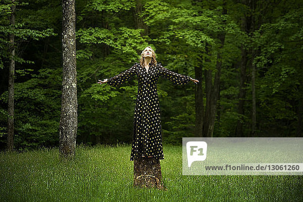 Woman with arms outstretched standing on tree stump in forest
