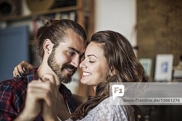 Glückliches junges Paar lächelt und hält zu Hause Händchen