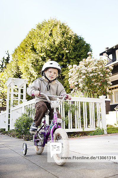 Portrait of boy riding bicycle on footpath