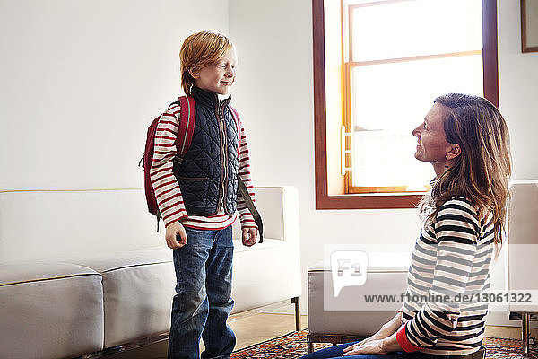 Boy with backpack looking at mother at home