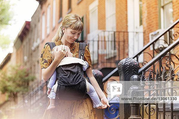 Mutter  die ihr Kind im Tragesitz hält  während sie gegen ein Haus läuft