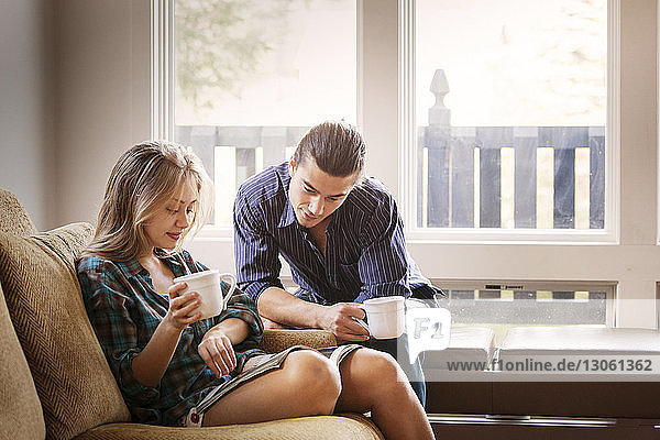 Couple reading magazine while drinking coffee at home