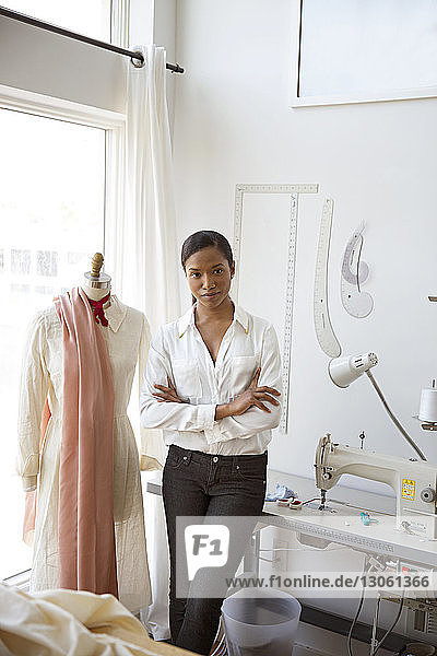 Portrait of confident woman standing by dressmaker's model in studio