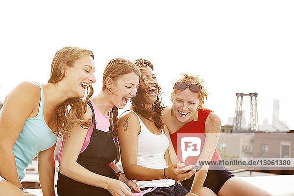 Frauen lachen beim Telefonieren auf der Gebäudeterrasse während eines sonnigen Tages