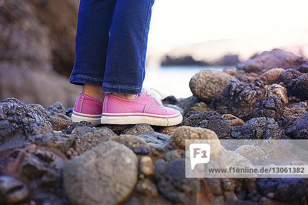 Low section of girl standing on rock