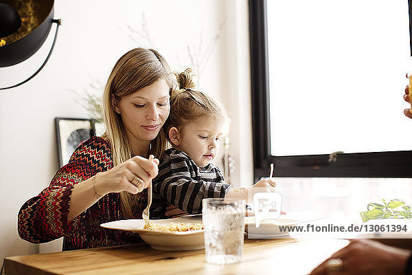 Mutter und Tochter beim Mittagessen am Tisch