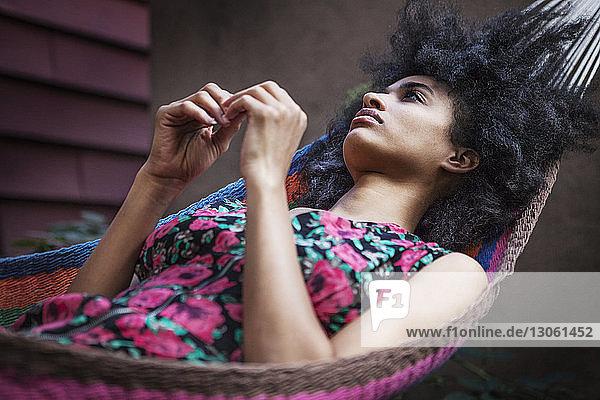 Nachdenkliche Frau entspannt auf Hängematte