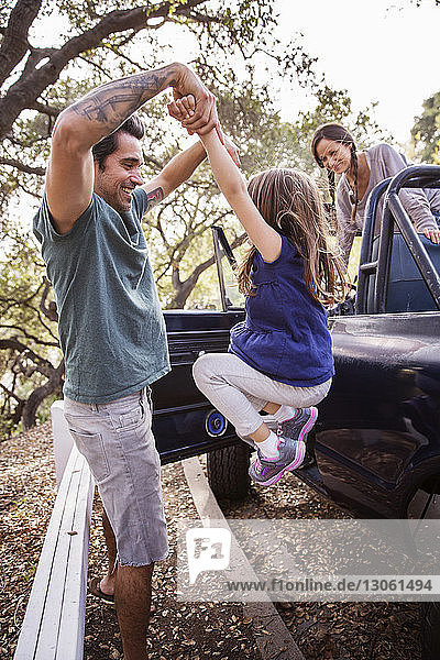 Vater schwingt Tochter,  während Mutter im Geländewagen steht