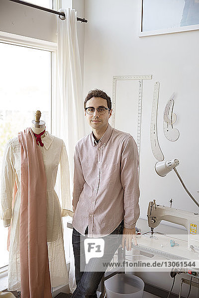 Portrait of confident man standing by dressmaker's model in studio
