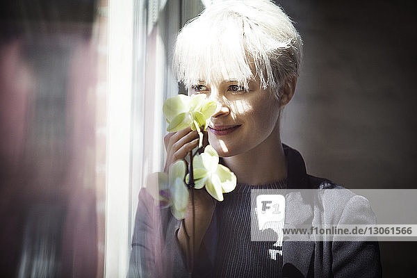 Thoughtful woman holding flowers while looking through window at home