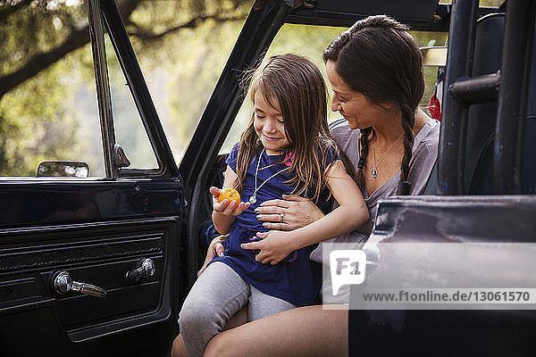 Glückliches Mädchen mit Orange sitzt im Pick-up auf dem Schoss der Mutter