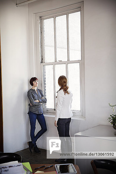 Female colleagues having discussion while by window in board room
