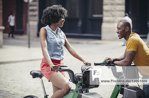 Couple talking while standing by bicycle rack