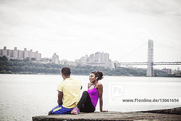 Ehepaar sitzt auf Pier am Flussufer