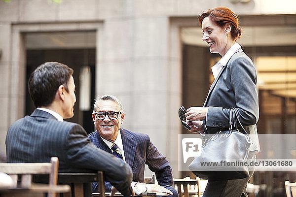 Glückliche Geschäftsleute unterhalten sich im Straßencafé
