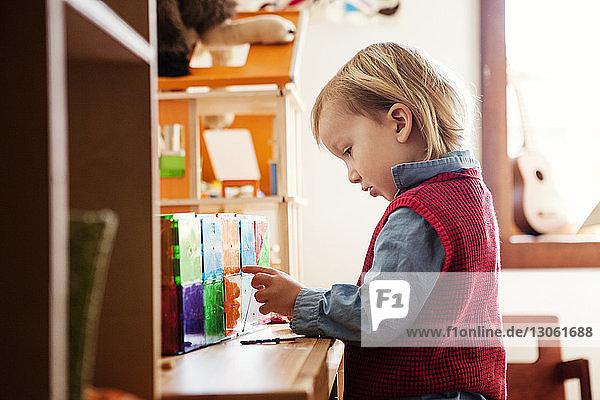 Seitenansicht eines Jungen  der am Tisch mit Spielzeug spielt