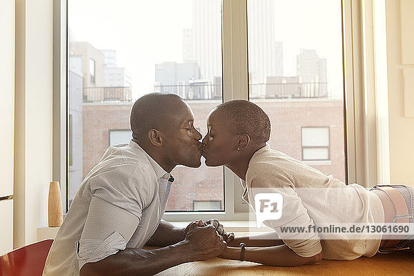 Side view of affectionate couple kissing at table against window home