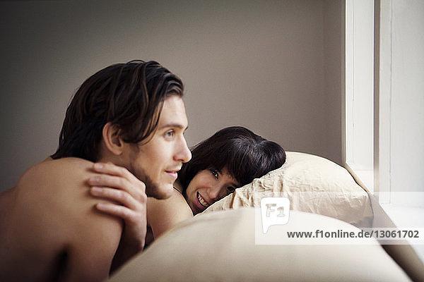 Mann schaut weg  während er bei seiner Freundin zu Hause im Bett liegt