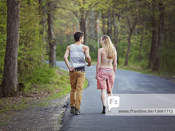 Rear view of couple talking while walking on road