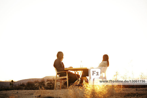 Low angle view of couple sitting on chairs against clear sky