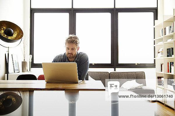 Mann mit Laptop am Tisch