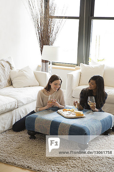 High angle view of friends enjoying snacks with wine while relaxing at home