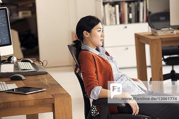 Geschäftsfrau entspannt sich auf Stuhl im Büro