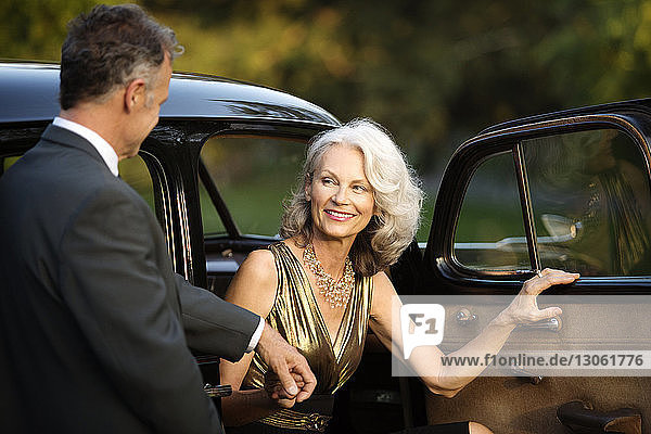 Happy senior woman holding man's hand while disembarking from vintage car