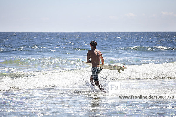 Man carrying surfboard in sea against sky