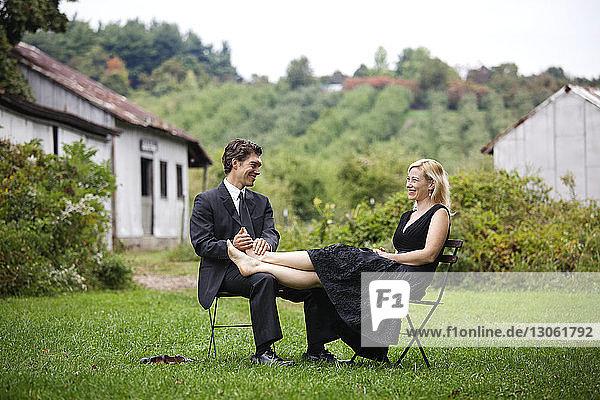 Mann hält Frauenfüsse  während er auf einem Stuhl auf einem Grasfeld sitzt