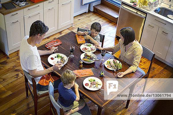 Hochwinkelansicht einer Familie  die am Esstisch in der Küche isst