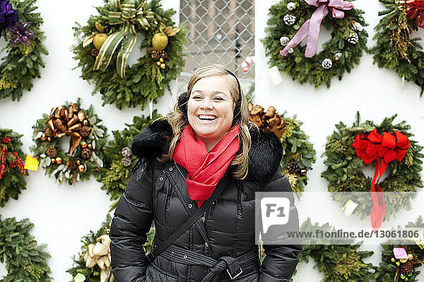 Woman in warm clothing while standing against Christmas wreath
