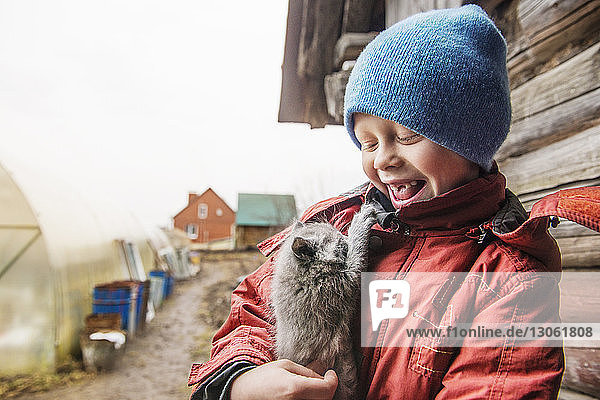 Happy boy carrying kitten while standing outside house